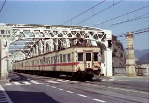 木曽川の鉄橋を渡る名古屋鉄道の特急。この橋は車も一緒に走っていました。1976年の写真です。